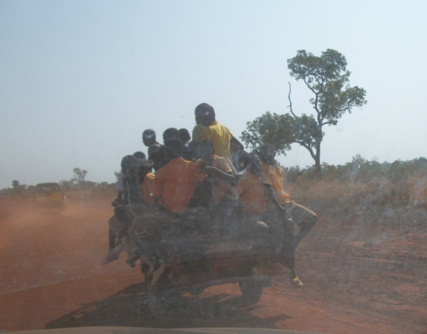 School children grabbing a ride on a motorcycle with trailer.